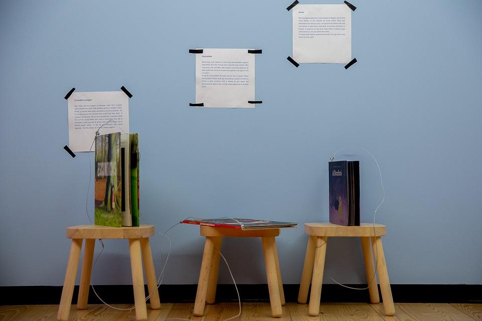 Três bancos com Livros espetaculares e textos da curadora Sara Amado colados na parede da biblioteca do público, no Entrepiso do LU.CA.