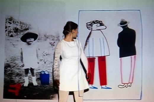 Madalena Marques olha por cima do ombro para os desenhos de um homem e uma mulher desenhados e projetados por Catarina Sobral, durante o espetáculo «Impossível».
