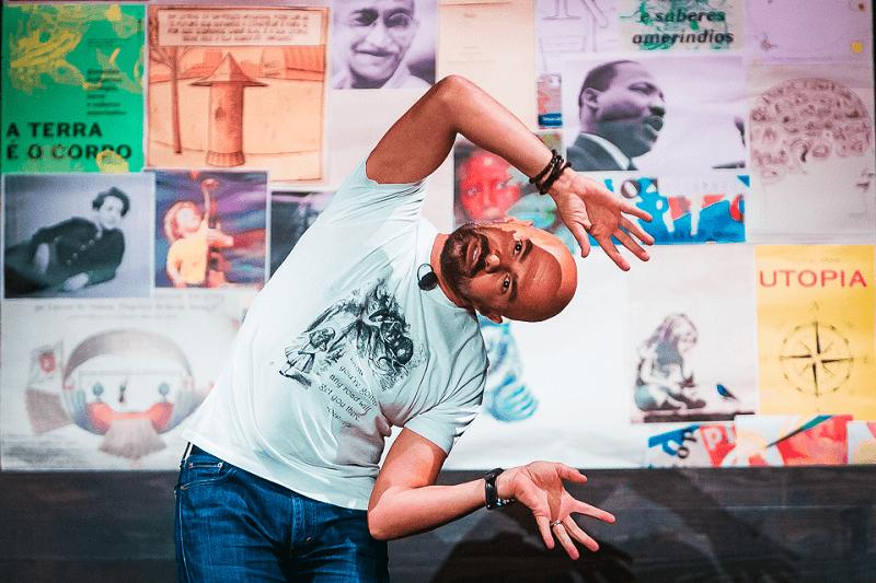 André Leonor, ator-orador da Miniconferência para Miúdas e Miúdos Curiosos Sobre a Utopia, flecte o tronco para a direita. Os seus braços dobram pelo cotovelo e as mãos estão abertas pela altura da cabeça. Na parede de trás, vêm-se fotografias de várias personalidades: Martin Luther King, Hannah Arendt, o menino com o cravo do 25 de Abril, entre outros.