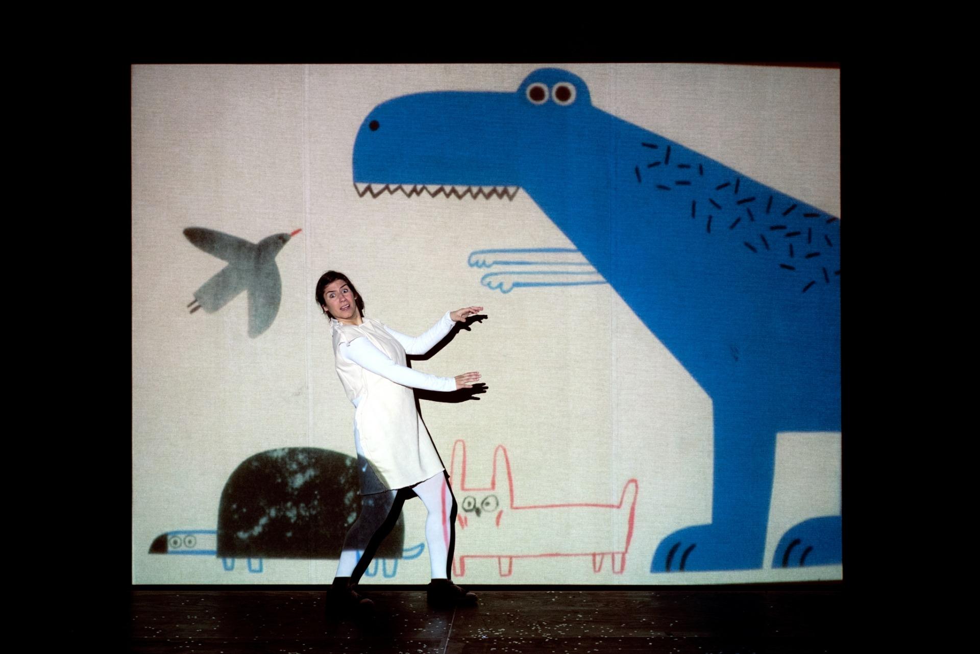 A atriz Madalena Marques interage com o desenho projetado de um dinossáurio.