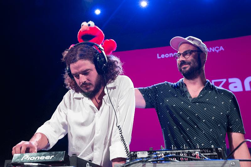 Divertido, Pedro Ramos apoia um boneco na cabeça de Tomás Wallenstein durante o DJ Set de ambos no LU.CA.