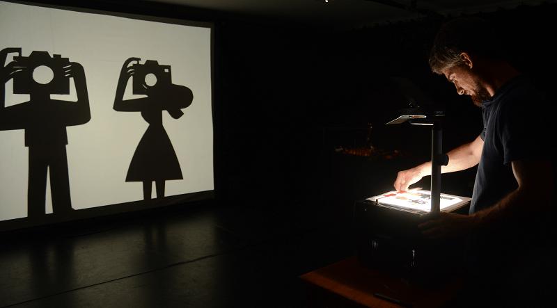 Através de um retroprojetor, João Fazenda projeta o desenho de um homem e uma mulher lado a lado, ambos apontando máquinas fotográficas no espetáculo Retrato Falado.