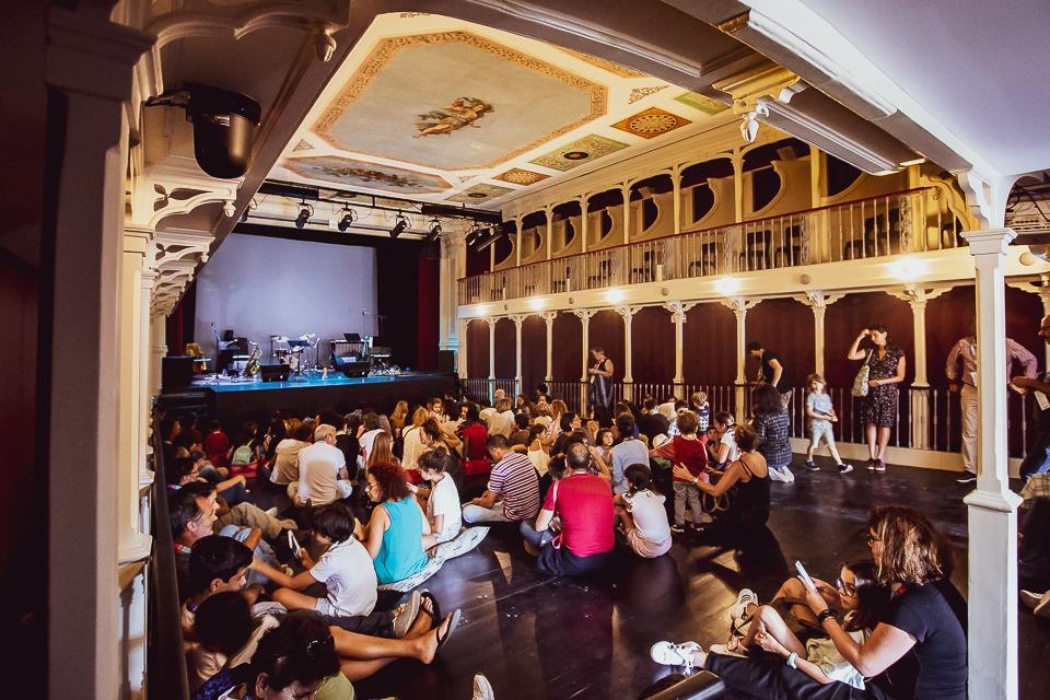 Sala de espetáculo cheia de crianças sentadas no chão.