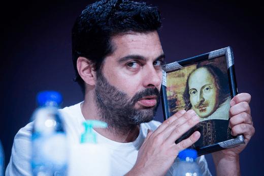 O ator segura, junto ao rosto, um desenho do dramaturgo inglês do séc. XVI, William Shakespeare enquanto olha de soslaio para a fotografia no espetáculo