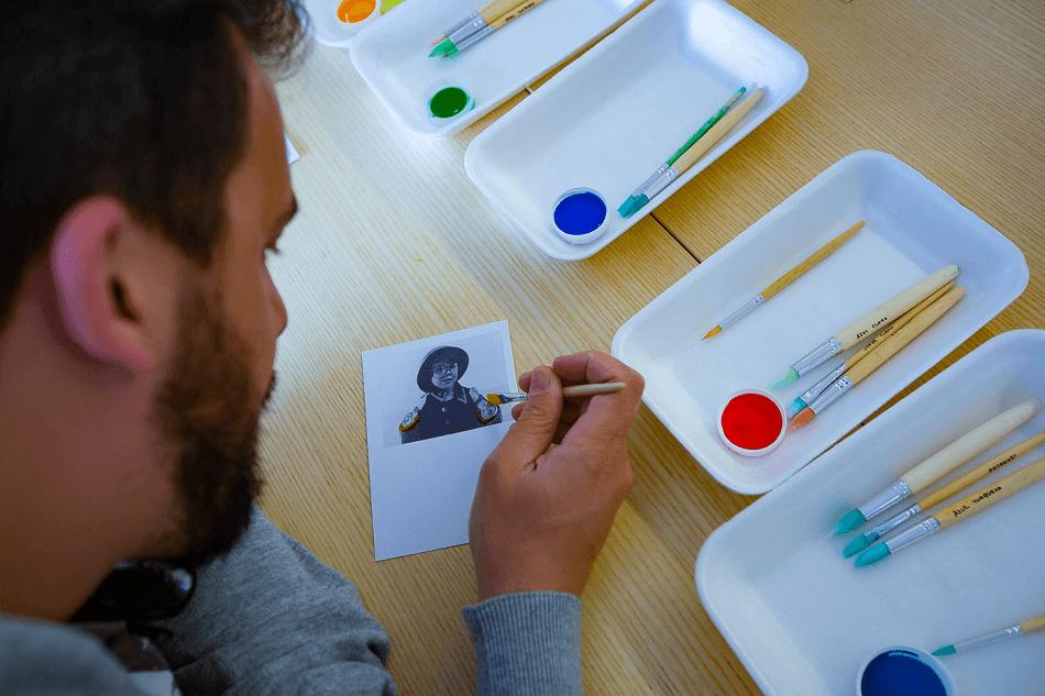 Um homem de barba pinta sobre uma fotocópia a preto e branco.