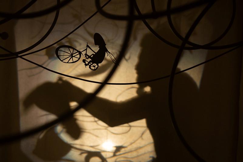 Fotografia de jogo de sombras entre o ator Filipe Caldeira e um recorte com a forma de um homem a andar de bicicleta.