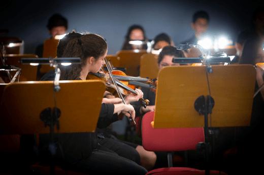 No primeiro plano, violista de perfil e, ao fundo, outros músicos da Orquestra Juvenil de Lisboa, durante o espetáculo
