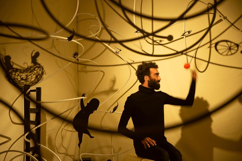Fotografia do espetáculo Catavento em que  ator Filipe Caldeira está rodeado de recortes e das suas sombras projectadas no pano de fundo.