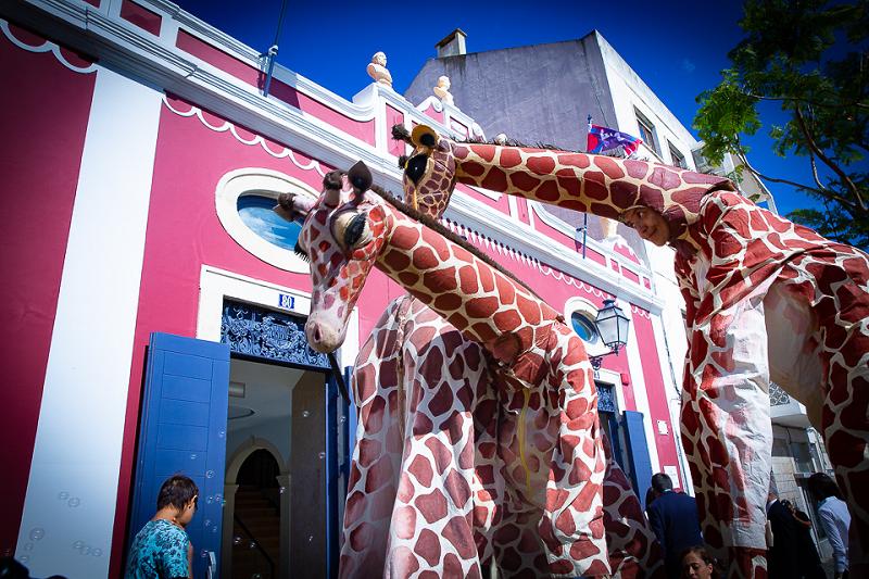 Três atores com fatos realistas de girafas passeiam-se entre os visitantes dos Dias da Inauguração do LU.CA.