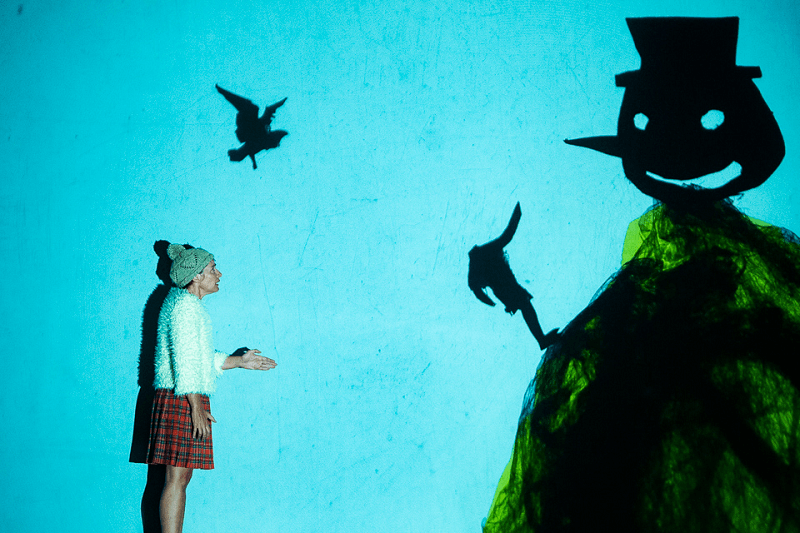 A atriz Ana Brandão interage com a projeção em tempo real do desenho de uma montanha encimada pela cabeça gigante de um boneco de neve. Um boneco sem cabeça sobe a montanha e aponta para a cabeça gigante lá no alto. Um pássaro voa na direção da montanha. Fotografia captada durante o espetáculo