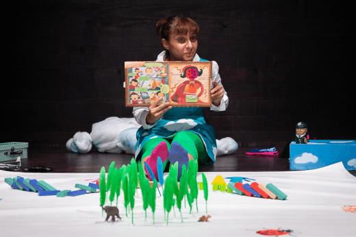 Atriz Margarida Gonçalves segura um livro. Aos seus pés, erguem-se pequenas árvores de papel verde. Imagem do espetáculo «Poemas de Pé para a Mão».
