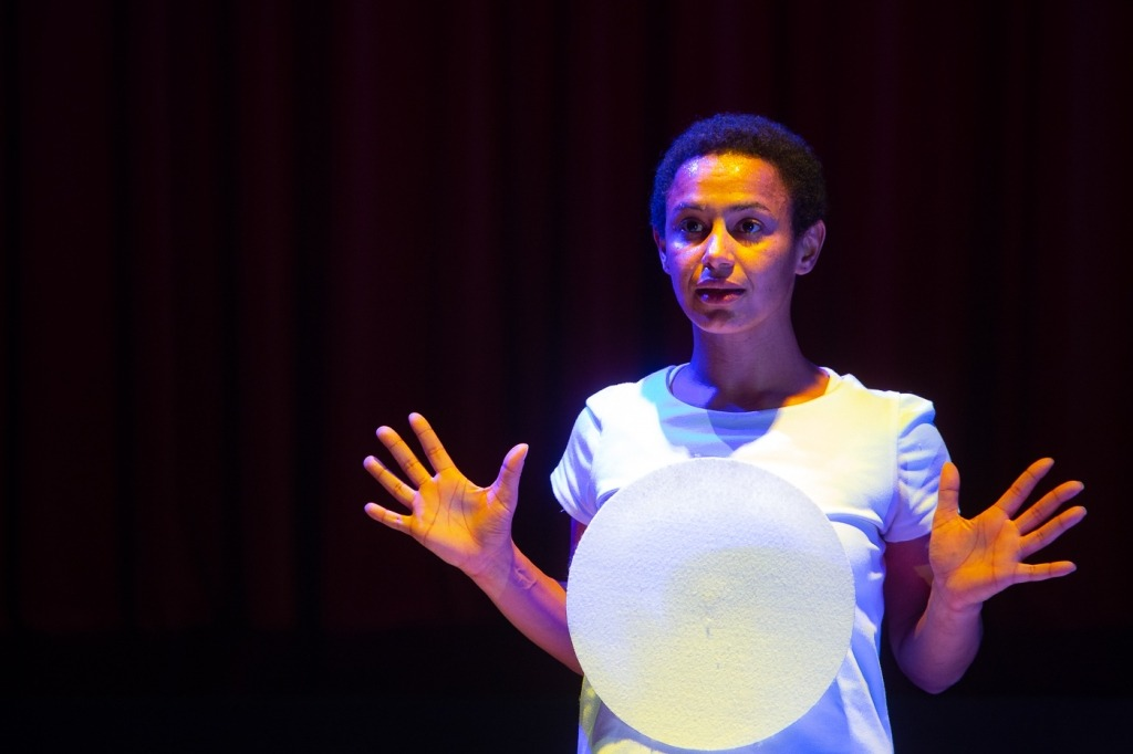 Rita Omar, a bailarina que representa Bianca, ergue as mãos pela altura dos ombros. Na sua frente, encontra-se uma esfera branca. Imagem captada no espetáculo Bianca Branca.