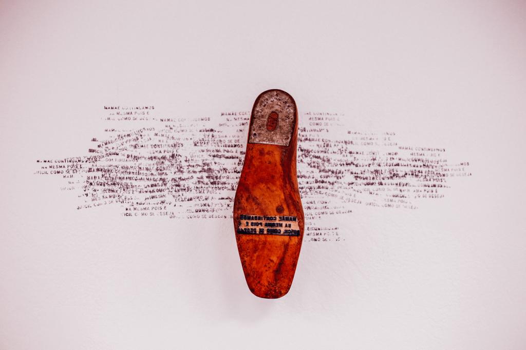 Fotografia frontal de parte da instalação Cartas de Madeira, de Keli Freitas. Uma forma de sapato com capa de metal na calcanheira e carimbo na zona da sola. Na parede atrás da forma, há impressões sobrepostas e desiguais do carimbo da forma que dizem «Mamãe continuamos/ na mesma pois é/ difícil como se deseja».