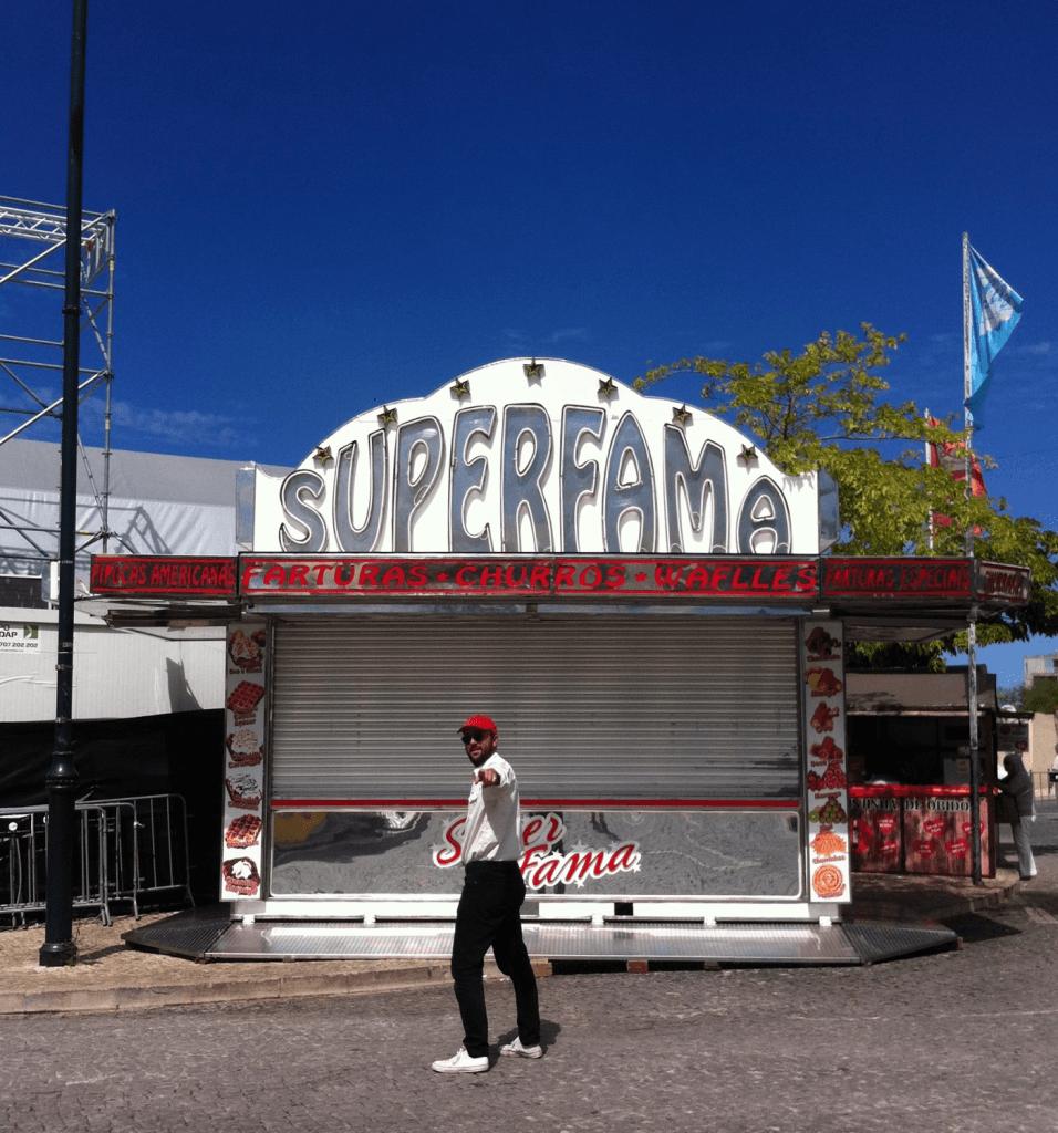 Fotografia tirada de dia. DJ Crazyman posa de perfil defronte da barraca de farturas «Superfama», que está encerrada.
