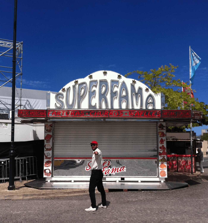 DJ Crazyman posa de perfil defronte da barraca de farturas «Superfama».