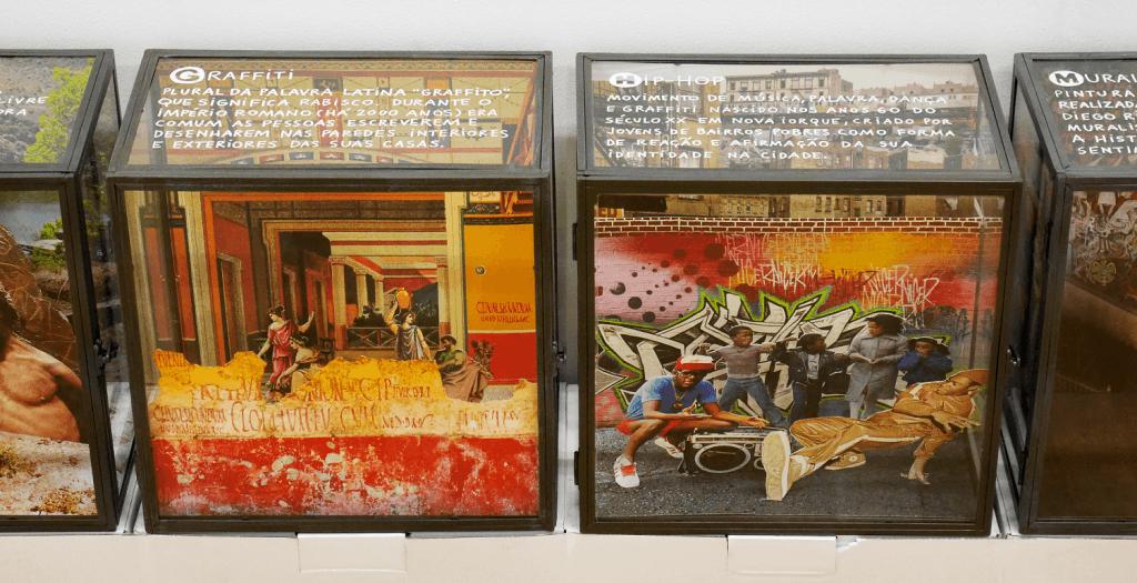 Caixas de vidro contendo imagens e maquetas em 3D com representações de graffitis, grupos de hiphop na rua, etc