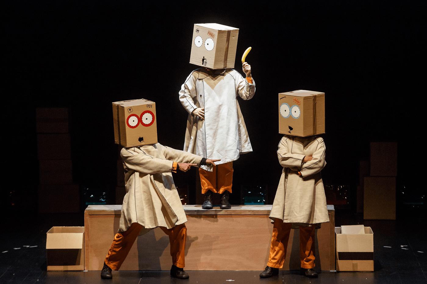 Três atores  da peça de teatro Frágil estão em cena com caixas de cartão sobre a cabeça.