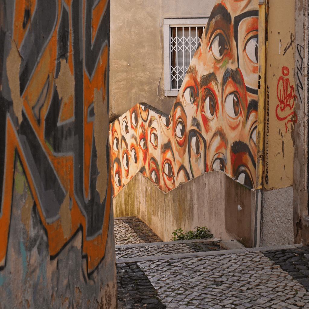 Escadas com empedrado à portuguesa com tag azul e laranja à esquerda e graffiti com um padrão de olhos sobre fundo amarelo à direita.