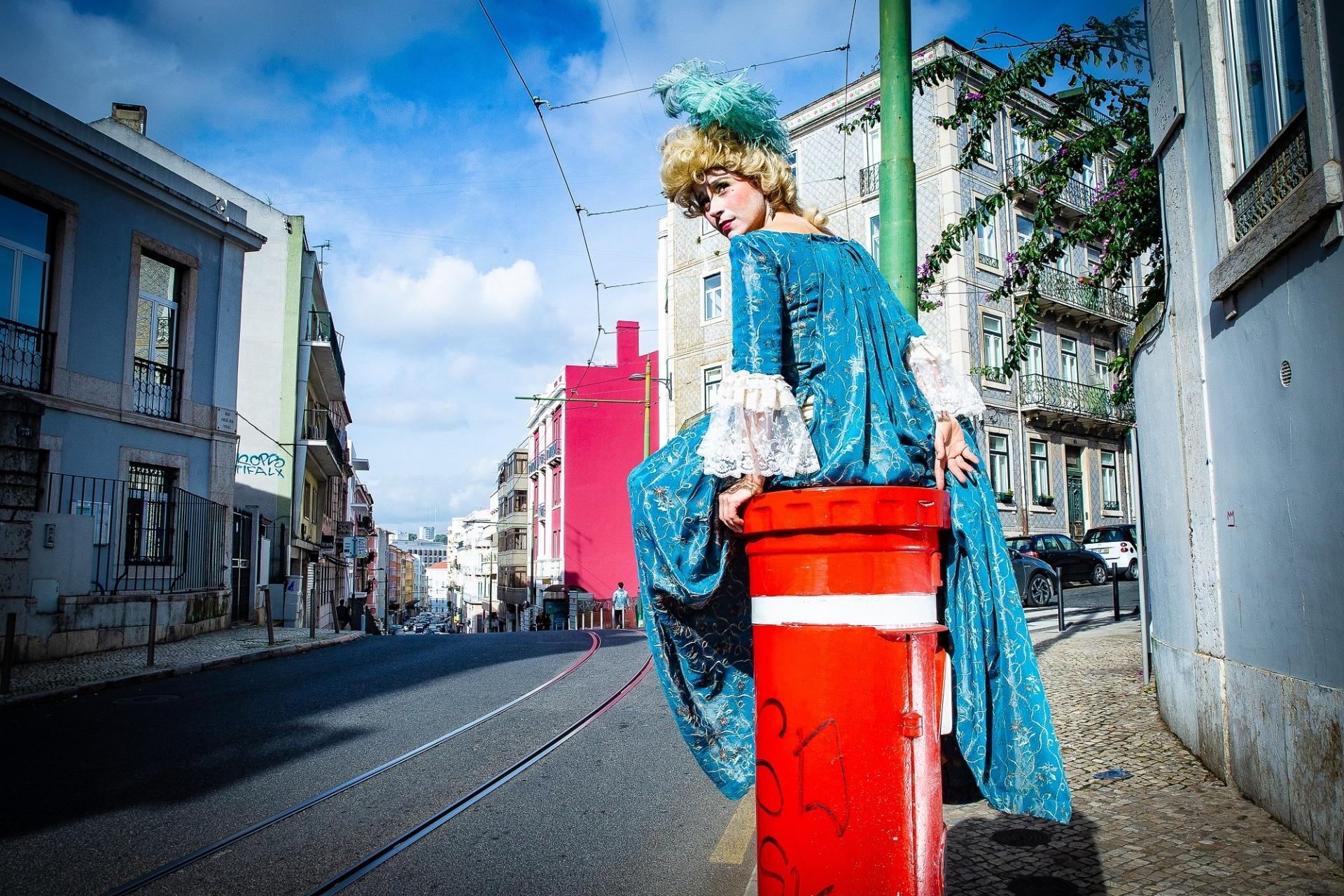 Com um vestido do século XVIII, a  atriz Crista Alfaiate está sentada num marco do correio.