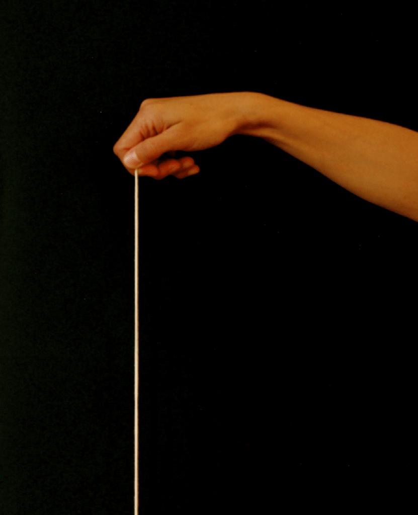 Uma mão segura um fio perfeitamente esticado na horizontal.