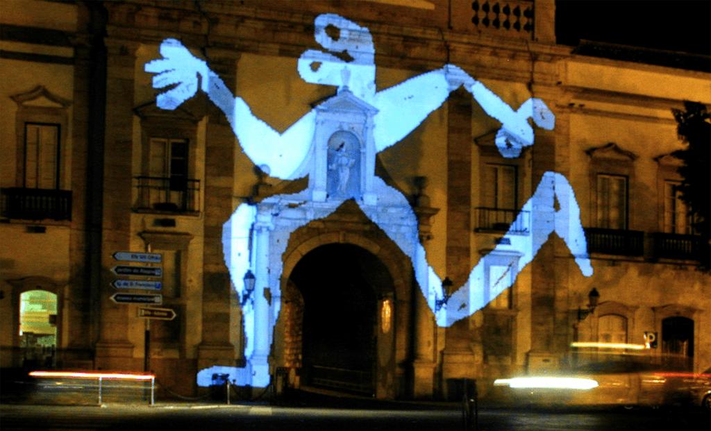 Figura antropormofizada e estilizada azul de dimensões colossais projetada, de noite, na fachada de uma igreja.