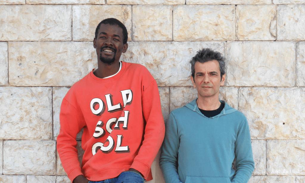 Da esquerda para a direita, o desenhador António Jorge Gonçalves e o MC e ativista Flávio Almada (ou LBC Soldjah) sorriem para a câmara, encostados a uma parede de pedra.