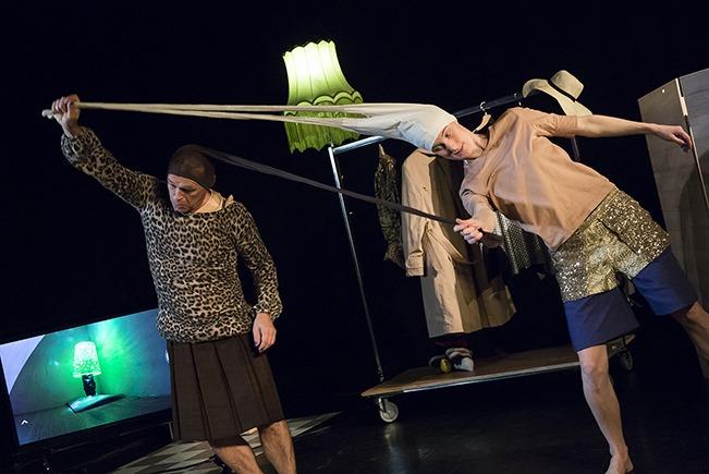 Fotografia de cena do espetáculo com dois atores, na qual um puxa umas meias collants que são utilizadas pelo outro ator como chapéu.