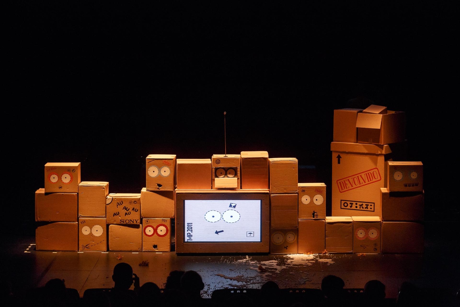 Caixas empilhadas em torno de um televisor com caras desenhadas.