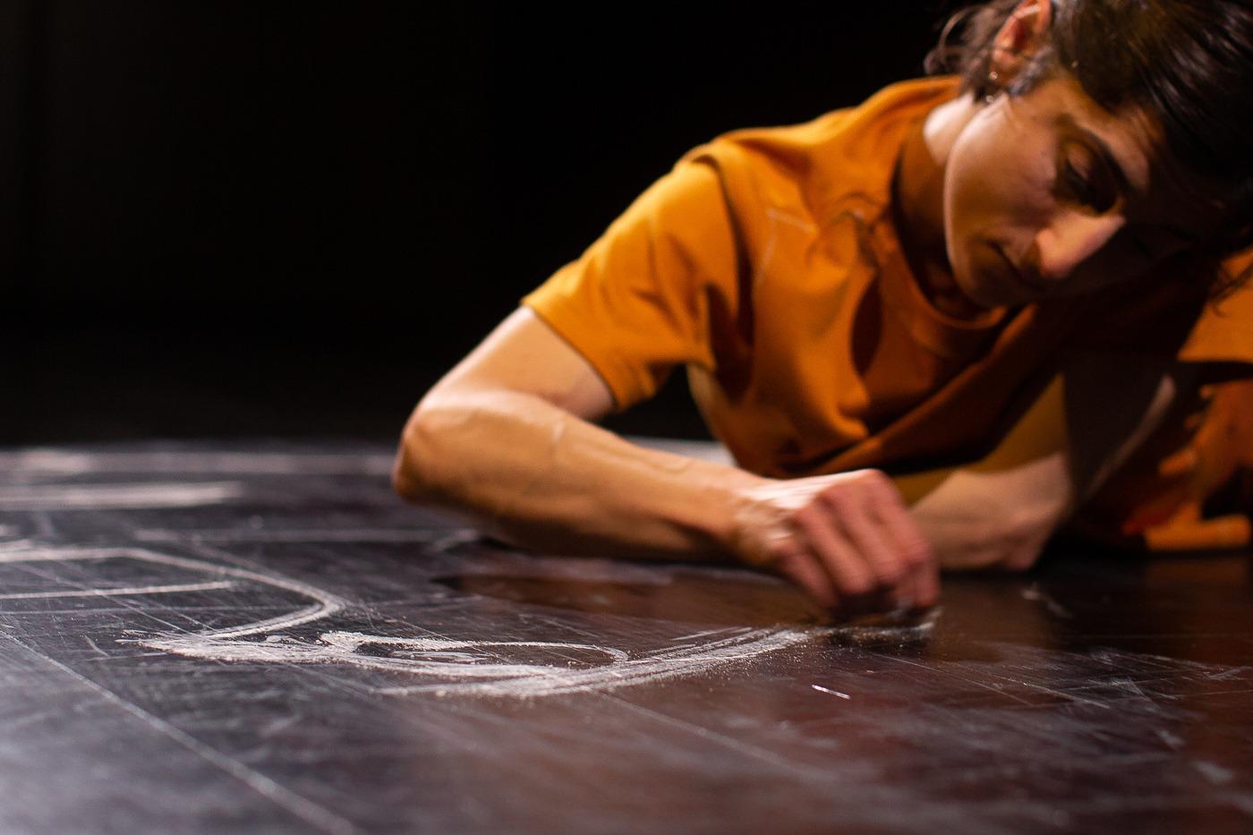 fotografia de cena do espetáculo sublinhar que retrata a bailarina Marta Cerqueira a desenhar no com giz branco no chão