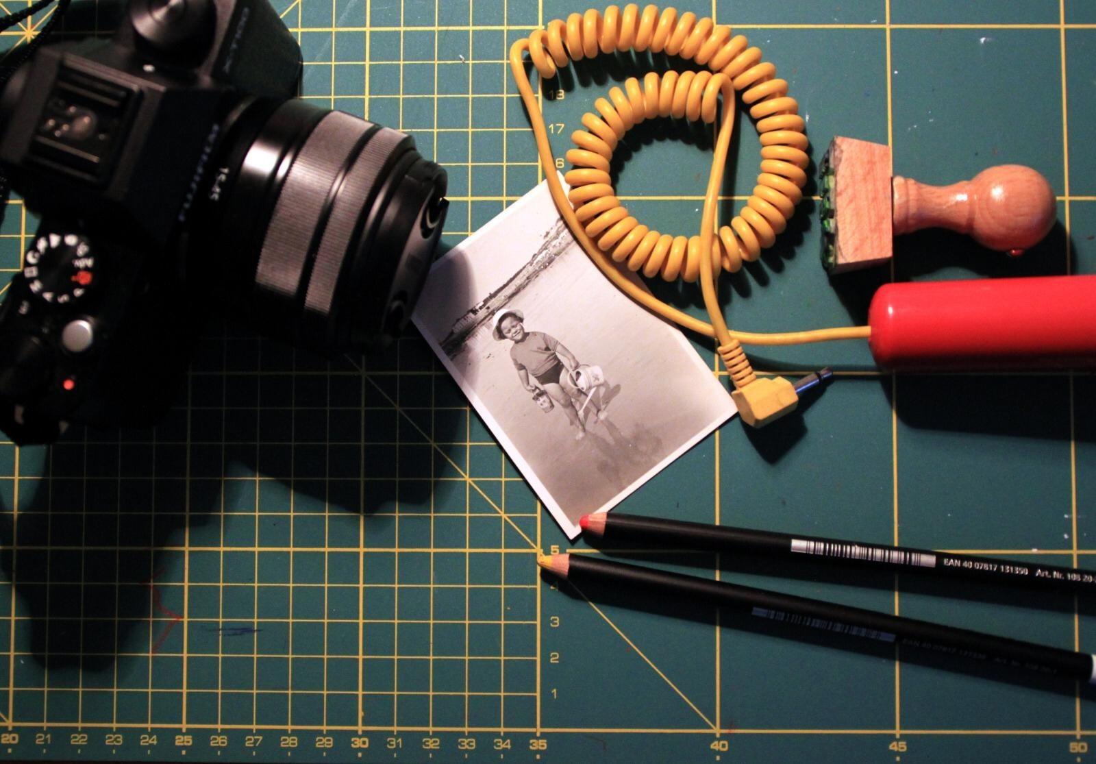 Fotografia com maquina fotografia, cabo de telefone, lápis e fotografia antiga.