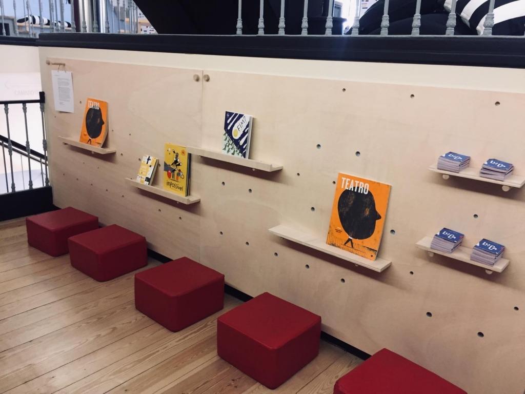 Fotografia do espaço da biblioteca do público com os livros do teatro