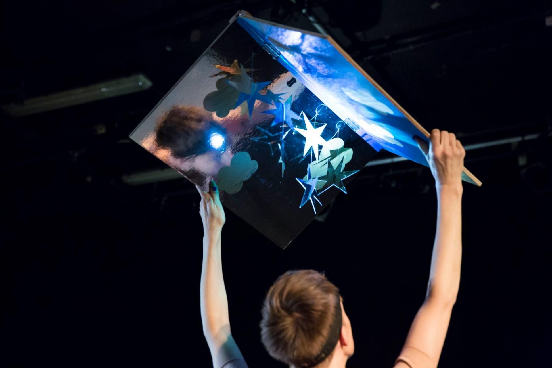 Fotografia de cena do espetáculo Eli & Rio, em que a actriz olha um livro aberto acima da cabeça.