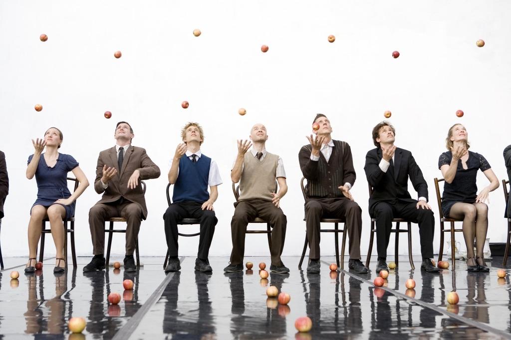 Retratao do espetáculo Smashed. 7 actores sentados em cadeiras fazem malabarismo com maçãs.
