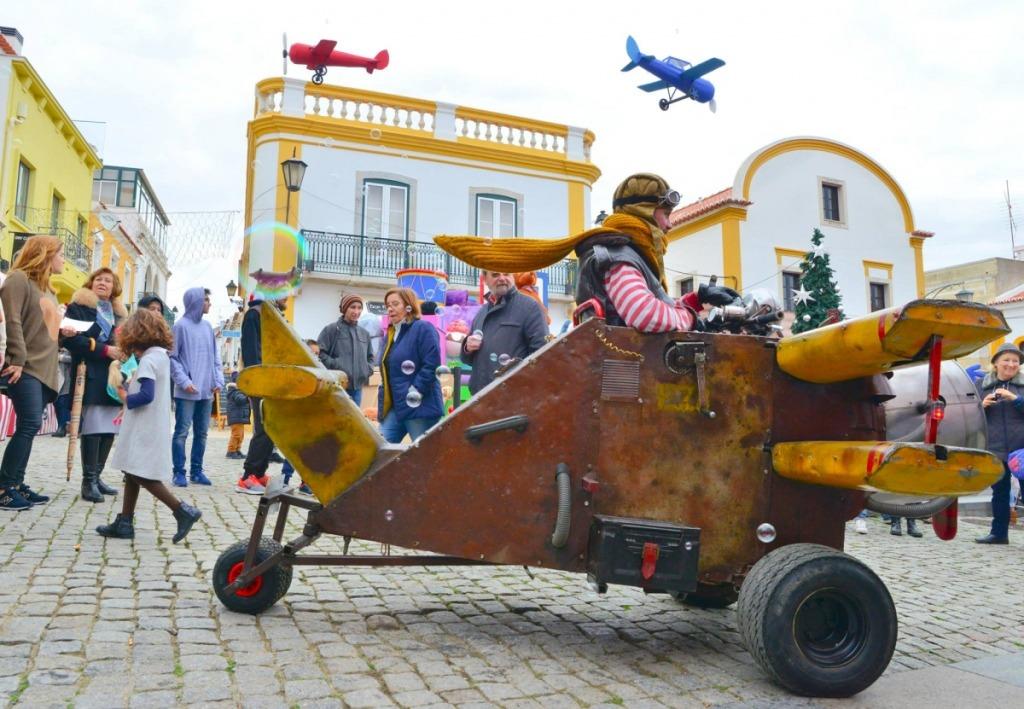 retrato do ez aviador. Na imagem está o avião estacionado numa praça com pessoas à volta. Vêem-se dois aviões no ar.