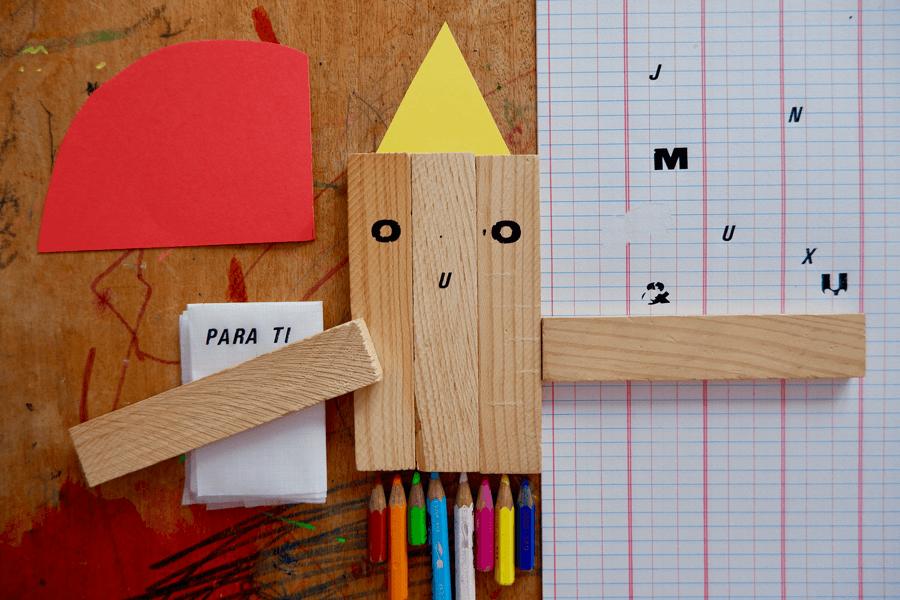 Cartolinas, pedaços retângulares de madeira, lápis de cor e folhas de papel dispostos numa mesa.