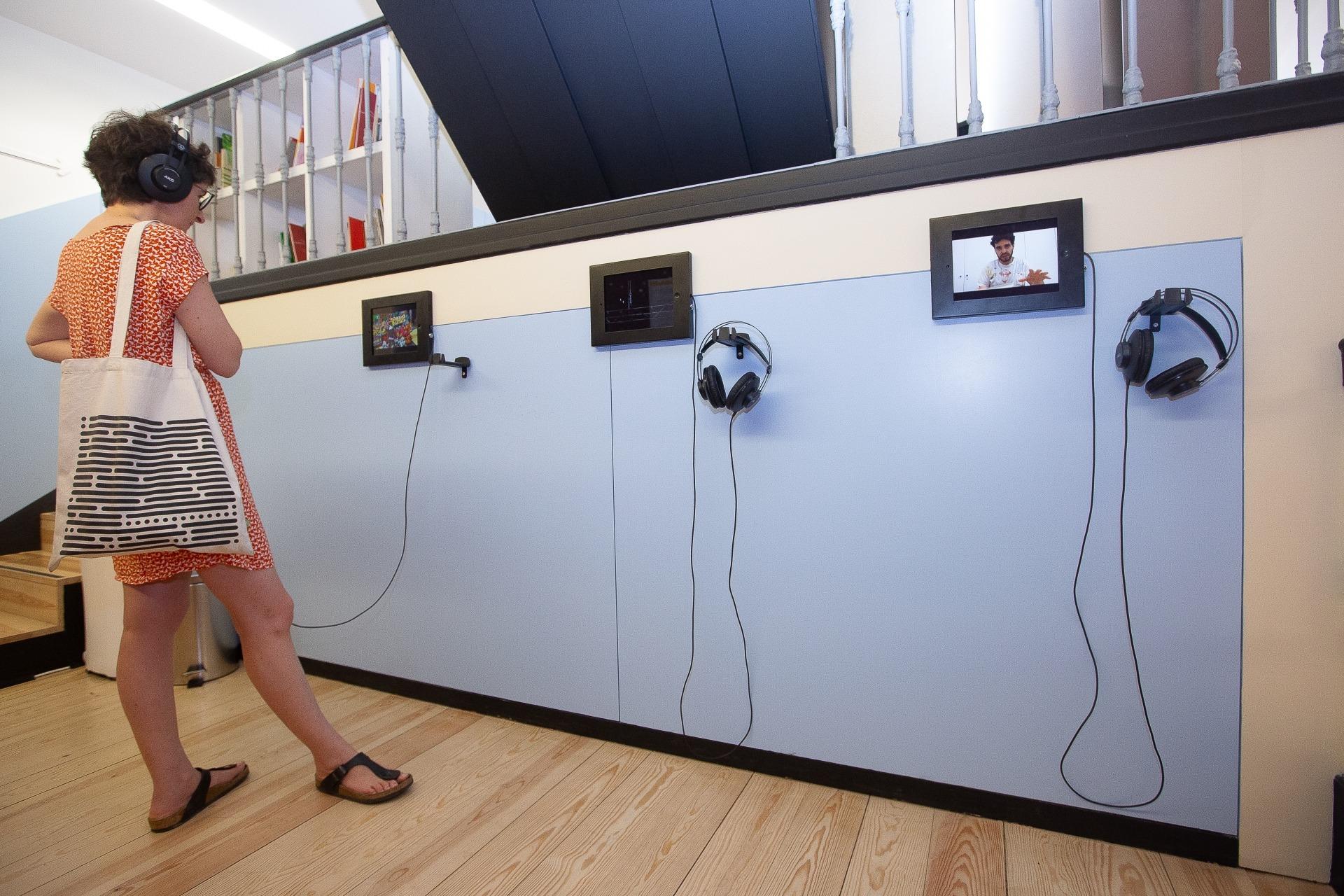Fotografia do espaço dos pontos de escuta: uma mulher com auscultadores olha para os três ipad na paredes.