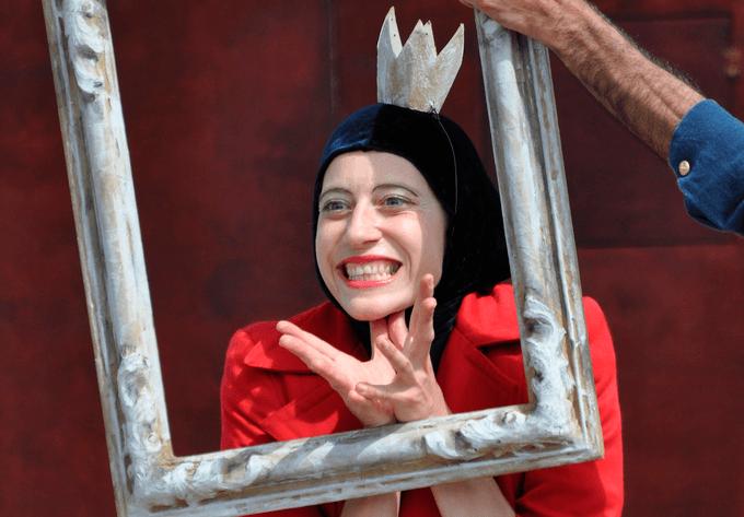 retrato de Julieta Rodrigues, vestida de vermelho com coroa no espetáculo Histórias Suspensas.