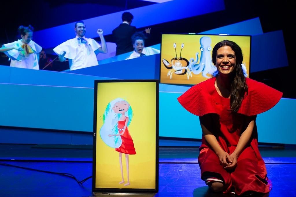 Foto de cena da menina do mar onde se vê no primeiro plano uma menina de vestido vermlho, com um ecrã de televisão ao seu lado com a sua imagem reproduzida na forma de uma ilustração animada.