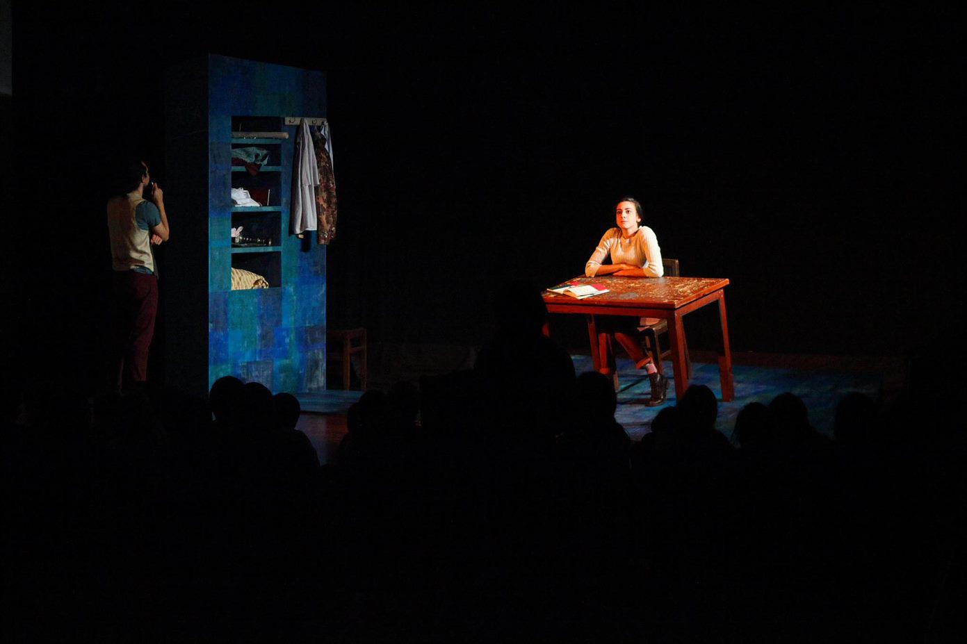fotografia de cena do espetáculo Mesa, onde vemos a atriz sentada a uma mesa iluminada com o restante palco às escuras.