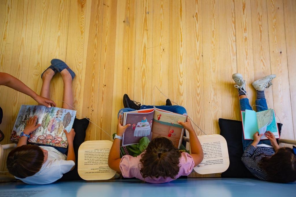Três crianças sentadas no chão lêem livros. Fotografia tirada de cima.