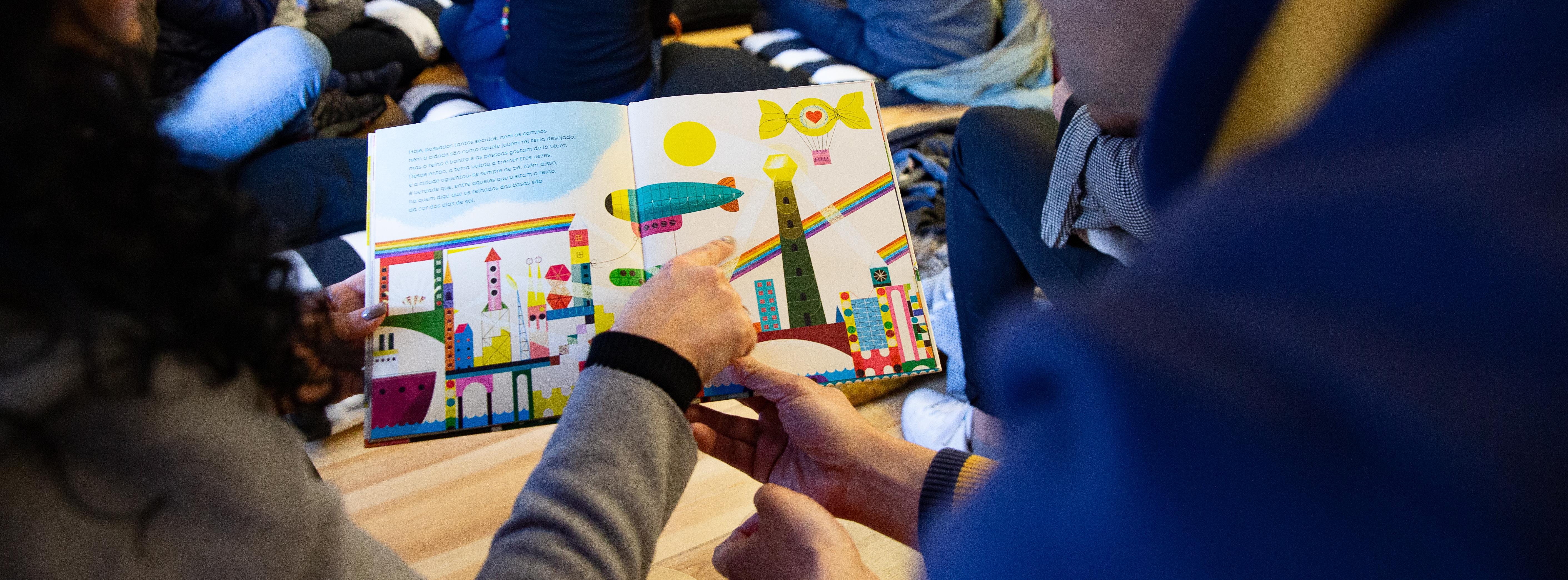 Duas pessoas seguram  um livro ilustrado aberto. Uma delas aponta para a imagem, com desenhos de uma cidade