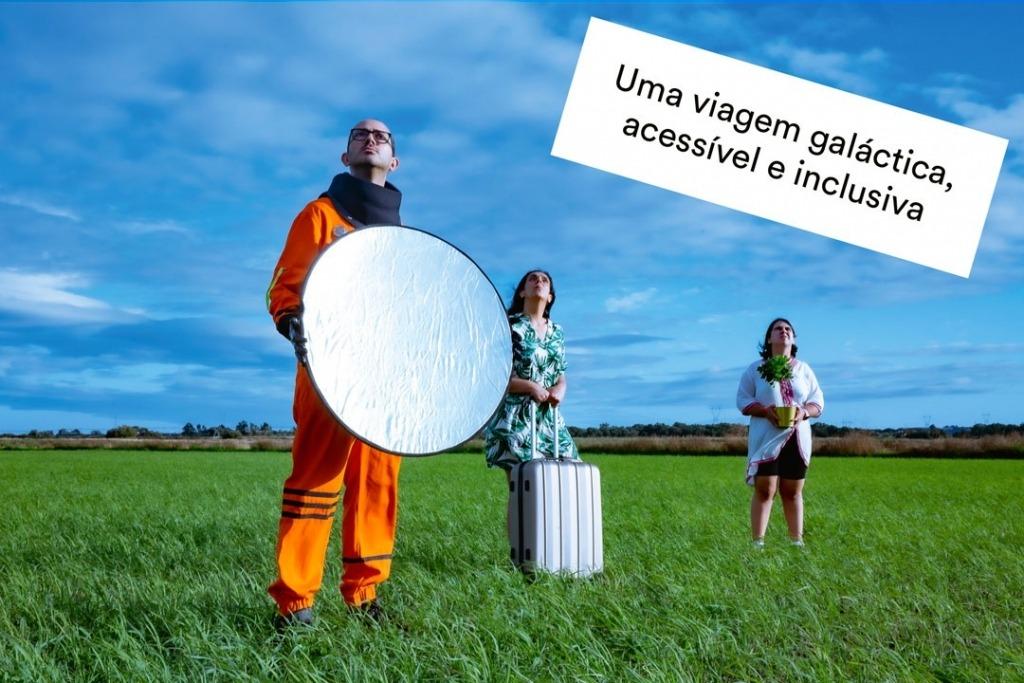 Três dos atores do Aldearã, no meio de um arrozal. Um está vestido de astronauta, uma agarra numa mala e a terceira uma planta.