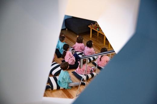 Pela fresta de uma janela, vemos um conjunto de crianças, sentadas em almofadas