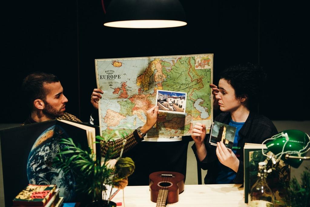 Fotografia de dois interpretes com um mapa da Europa aberto entre eles, uma  planta e um cavaquinho.