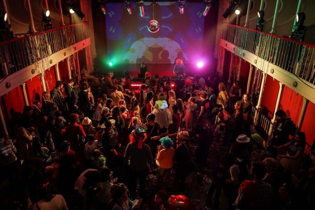 Fotografia do baile de carnaval de 2019 no Lu.Ca. Na imagem tirada dos camarotes vêm-se muitas crianças e adultos a dançar na sala do Lu.Ca.