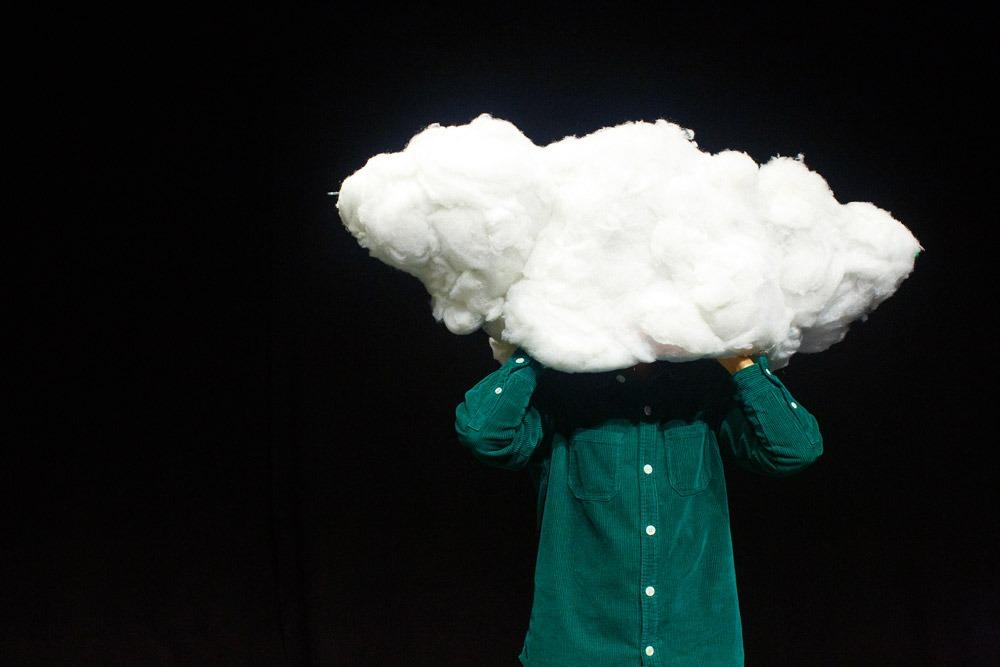 Fotografia de cena do ator Raimundo Cosme com um objeto cenográfico que é uma nuvem branca, em frente da cara.